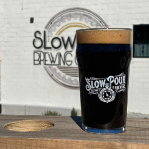 Slow Pour brew in front of their logo wall